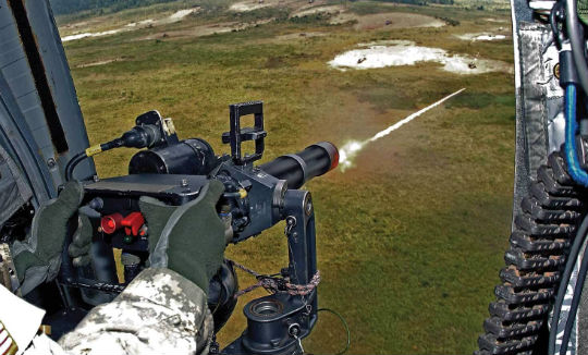 A student door gunner mans an M134 minigun. Instructors onboard the Chinook present the students with a mix of weapon jams, electrical problems, and more.