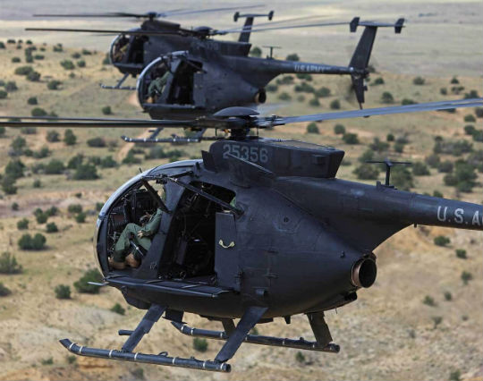 """A formation of three MD Helicopters MH-6M Little Birds from the Special Operations Aviation Training Battalion. MH-6M training is heavily focused on airborne assault; note the """"pods"""" to carry personnel externally and the fast rope bars. Ted Carlson Photos"""