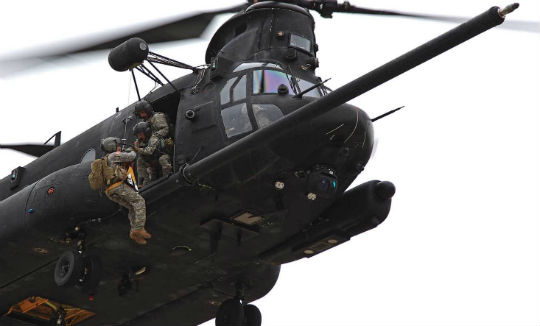 A SOATB MH-47G lifts up a medic using the hoist. Most Night Stalker medics spend the majority of their time on Chinooks.
