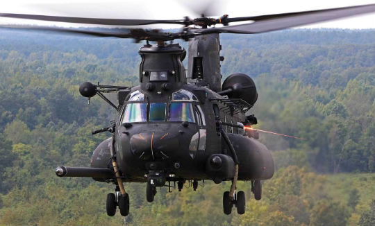 A Boeing MH-47G Chinook opens up with a M134 minigun. The weapon is used for suppression fire during infiltration and exfiltration missions. It may also have an additional pair of ramp-mounted M240 machine guns.