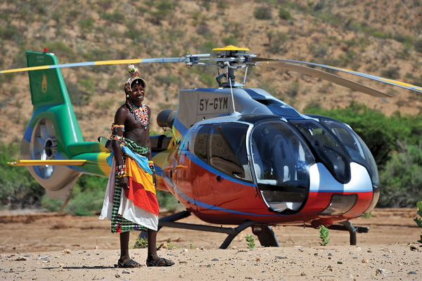 A Samburu warrior poses briefly in front of an equally colorful EC130. The author traveled to virtually every corner of Kenya during his time with Nairobi-based Lady Lori Helicopters.