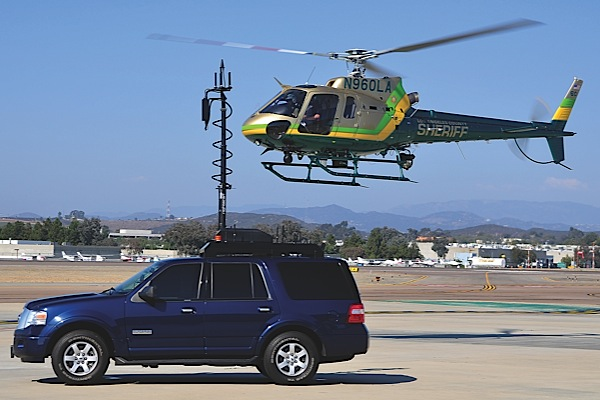The Los Angeles County Sheriffs Department (LASD) is a Helinet Technologies customer. Here, a downlink-equipped LASD AS350 B2 hovers near a Sheriffs tactical incident downlink vehicle.