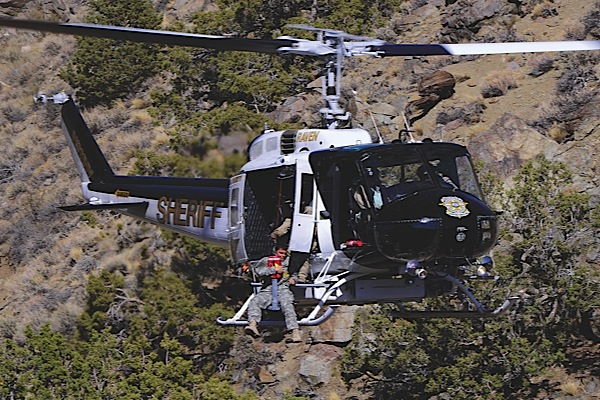 Working from the desert to the Sierra Nevada Mountains, the Washoe County Sheriffs Office Regional Aviation Enforcement Unit has a large range of mission profiles. Here, the Sheriffs HH-1H Huey performs a hoist rescue in the high deset region.