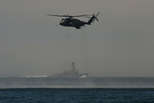 A MH-53E pulls a MK-103 device as a U.S. Navy destroyer works in the background.