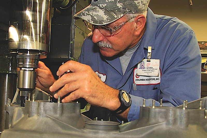 Jerry Fairchild adjusts the head of a milling machine prior to working on a combining transmission case from a 107.