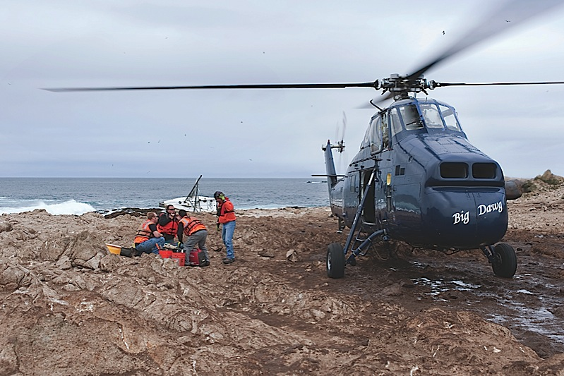Members of the salvage crew huddle next to Aris Helicopters S-58T on a rocky beach on the Farallon Islands to discuss preparations for salvaging a 38-foot sailboat in which five crewmembers lost their lives.