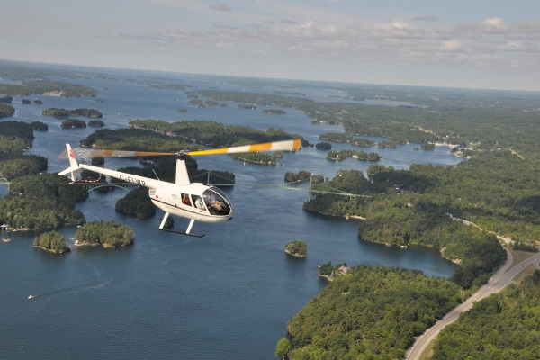 A Kouri's Kopters Robinson R44 flies tourists over the 1000 Islands bridge which spans the St. Lawrence River between Ontario and New York state.