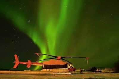 Bell 407 and AS350 B2 under a stunning northern lights display in Norman Wells
