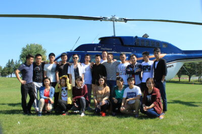 Chinese students pose in front of helicopter.