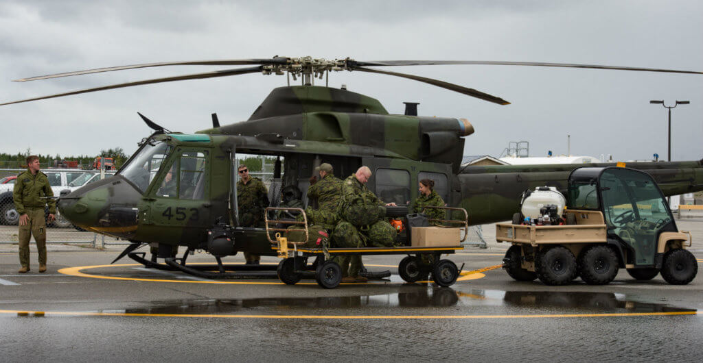 Canadian Armed Forces members unload a CH-147 helicopter from 1 Wing 408 Tactical Helicopter Squadron from Canadian Forces Base Edmonton, Alta., during Operation Nanook at Erik Nielsen Airport in Whitehorse, Yukon. Cpl Chase Miller Photo