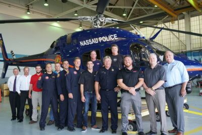 A group of people stands in front of a Nassau Police helicopter
