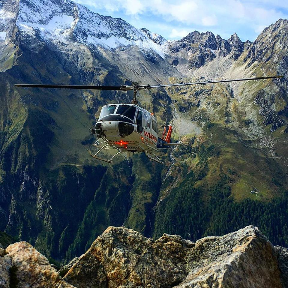 Helicopter flies in the foreground -- going vertical while snow on the peaks above gives way to the green below.