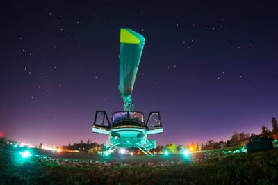 Helicopter resting on ground at night, partially illuminated by lights
