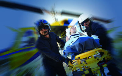 Two paramedics move a woman lying on a stretcher.