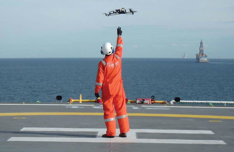 A Sky-Futures unmanned aerial vehicle (UAV) deployment team member releases an aircraft off the helipad of an offshore platform. The company uses a variety of UAVs for different work, but its current offshore UAV is the AscTec Falcon 8. Sky-Futures Photo