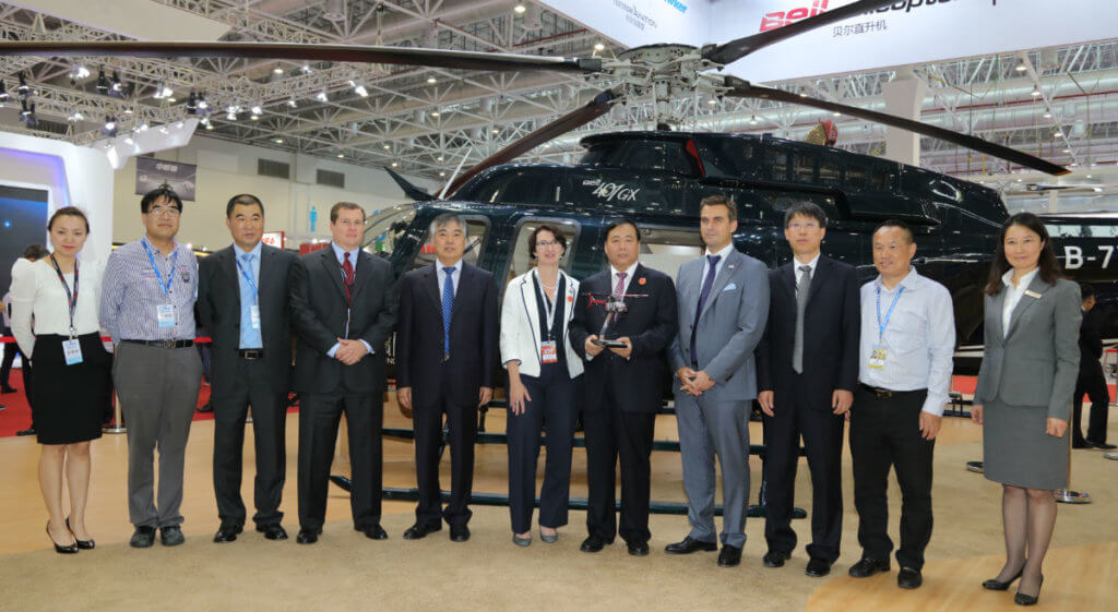 After the signing ceremony, Huaihe Sun (second from left), Xiaoning Yuan (fifth from left), Rachael Bedlington (sixth from left, Feng Jiang (seventh from left), and Patrick Moulay (eight from left) joined for a group photo. Bell Helicopter Photo