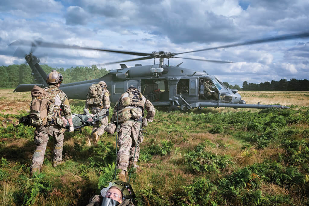 57th Rescue Squadron pararescuemen carry and drag simulated casualties towards the waiting 56th Rescue Squadron HH-60G Pave Hawk.