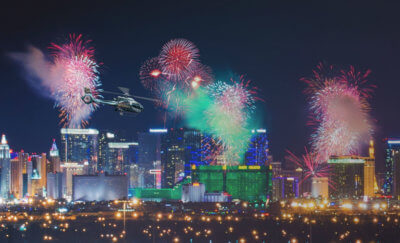Helicopter flies through cityscape with fireworks exploding around it.