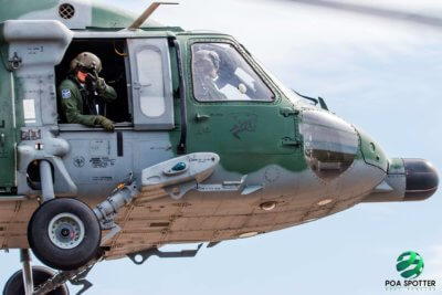A passenger makes a peace sign to the camera from the open window of a helicopter in flight.