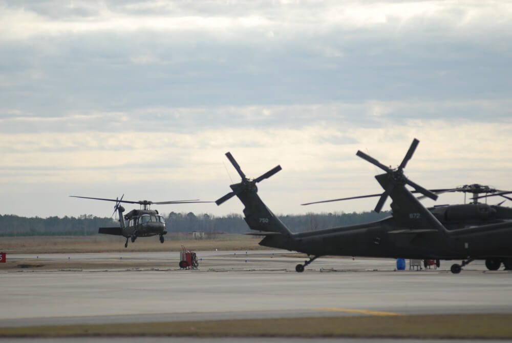 Two helicopters on an airfield.