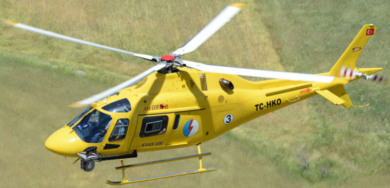Yellow AW119 helicopter with TrakkaCam mounted on it, in flight.