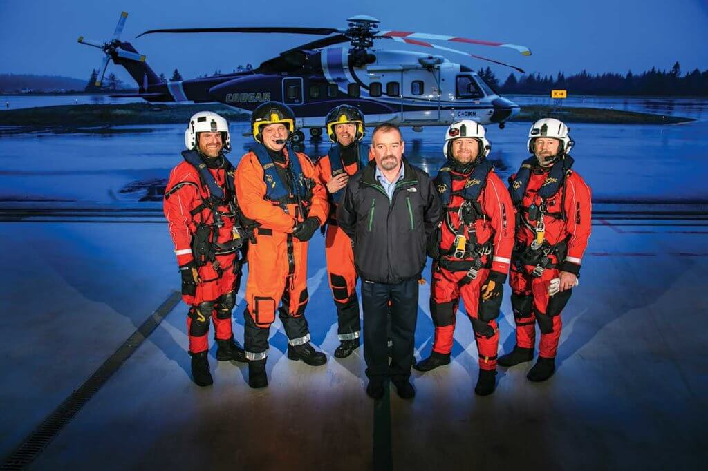 Rick Banks, Cougar's search-and-rescue program manager, stands in front of a SAR crew in the company's custom-built search and rescue hangar in St. John's. Heath Moffatt Photo