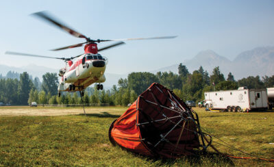 Columbia helicopter in background with firefighting bucket lying on ground