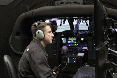 CWO 2 Travis Vanlengen monitors a pilot's flight at the Camp Dodge Joint Maneuver Training Center, in Johnston, Iowa. The instructor-operator's screens allow him to see the pilot inside the aircraft, as well as watch their flight path on a map, while controlling stress factors, such as inclement weather, enemy fire and mechanical failures. Vanlengen said these safety hazards are possible, both in peacetime and at war, and can be fatal without the proper training. Sgt Christie Smith Photo
