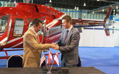 Capt Heru Susatyo, Air Pacific Utama, and Patrick Moulay, executive vice president, global commercial sales and marketing, celebrate the recent signing at Rotorcraft Asia. Bell Photo