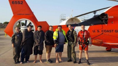 Coast Guard aircrew members take a photo with four people whose vessel capsized 15 miles north of Port Mansfield, Texas, Sunday morning on Apr. 30, 2017. U.S. Coast Guard Photo