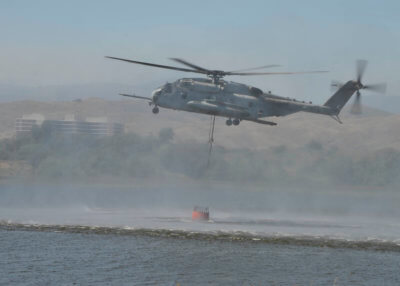 """A CH-53E Sea Stallion from the """"Flying Tigers"""" of Heavy Helicopter Squadron 361 pulls water from Lake O'Neill into a 420-gallon suspended bucket during a demonstration at the 2017 Wildland Firefighting Exercise at Lake O'Neill."""
