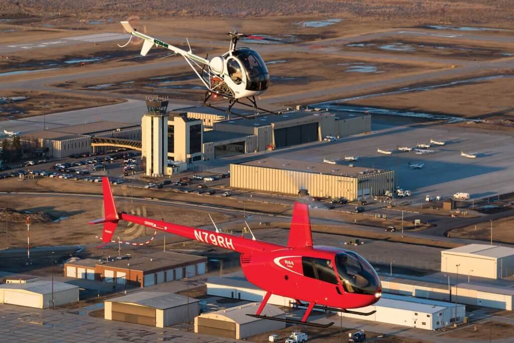 UND operates the S-300 and Robinson R44 in its fleet. Here, the two types fly with the UND aerospace airport campus in the background.
