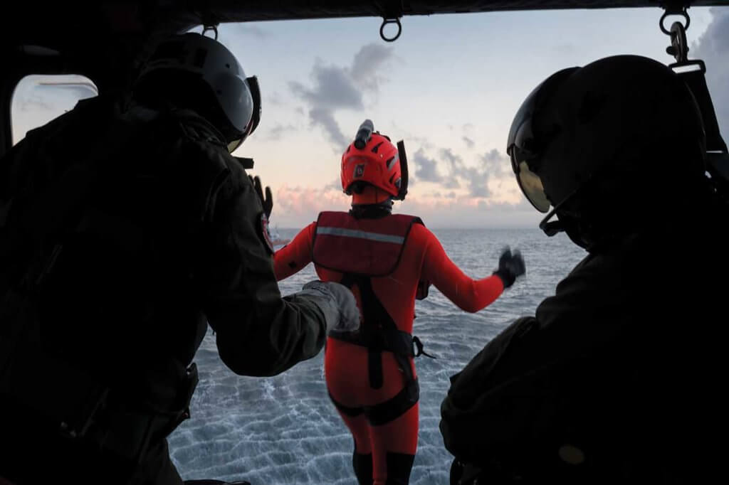 A rescue swimmer leaps from the AW139 into the ocean below during a training exercise.