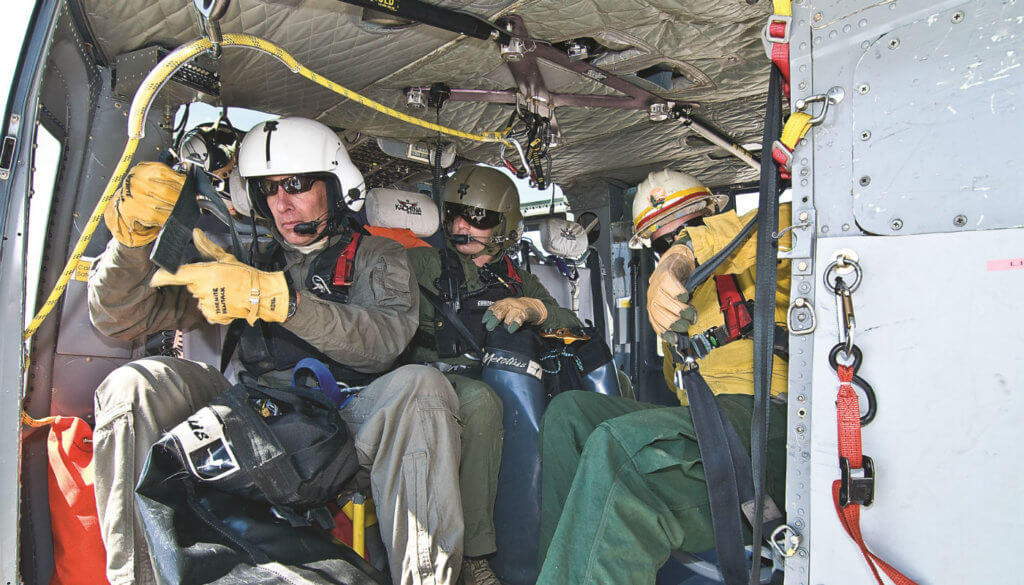 Rangers Jack Hoe flich and Chris Bellino, with spotter Boots Davenport, ready the cabin for heli-rappel training out of Yosemite's helibase at Crane Flat.