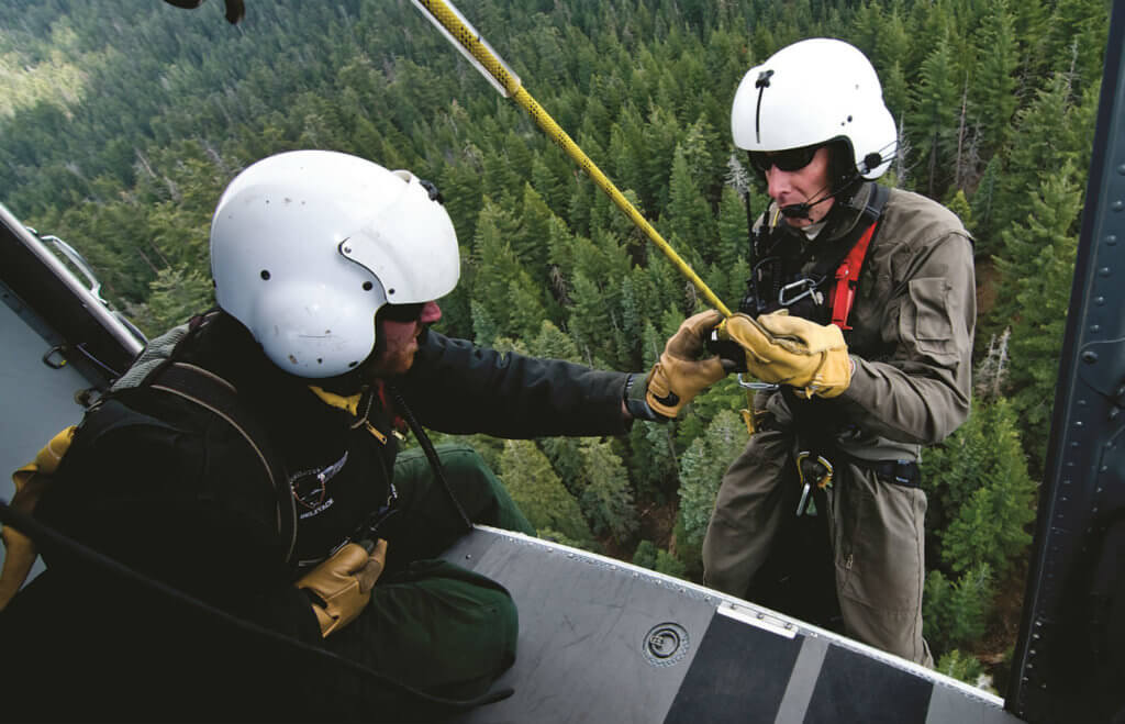 Ranger Jack Hoeflich is checked by Boots Davenport just prior to dropping down between the trees.