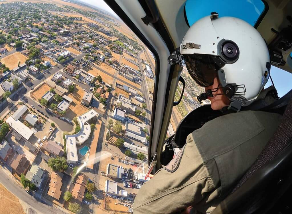 Man in cockpit of helicopter, wearing white helmet.