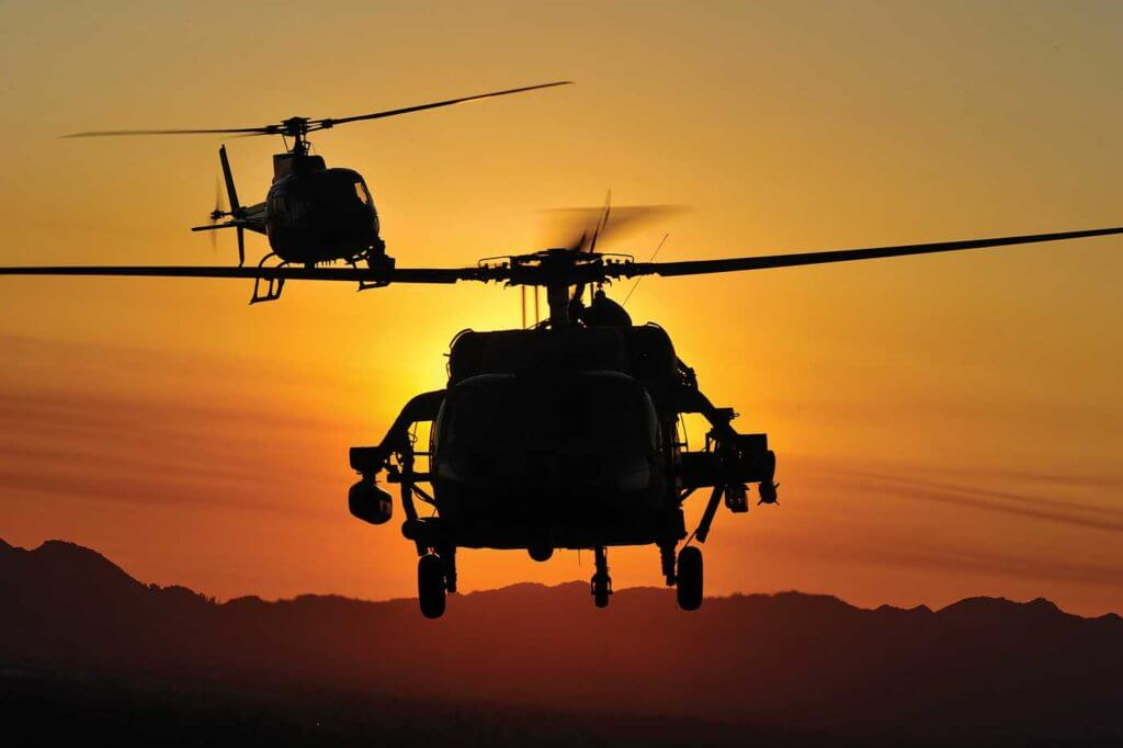 The Movie Hawk is chased by an Airbus AS350 B2 camera ship as the sun sets over Los Angeles.