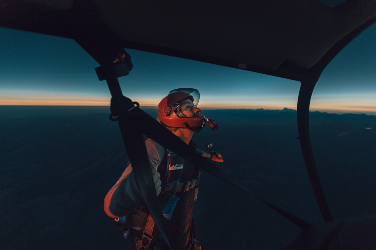 "GoPro athlete Chris Farro watches the total solar eclipse from the skids of York Galland's Robinson R66, ""moments before jumping into the eeriest sky I have ever seen."" Abe Kislevitz Photo / Instagram: @abekislevitz"
