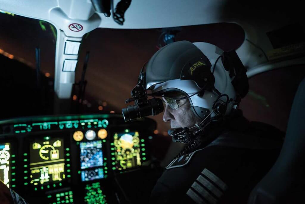 Pilot sits in darkened cockpit.