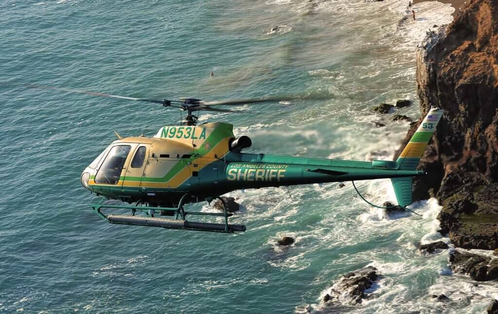 Helicopter in flight over coastline