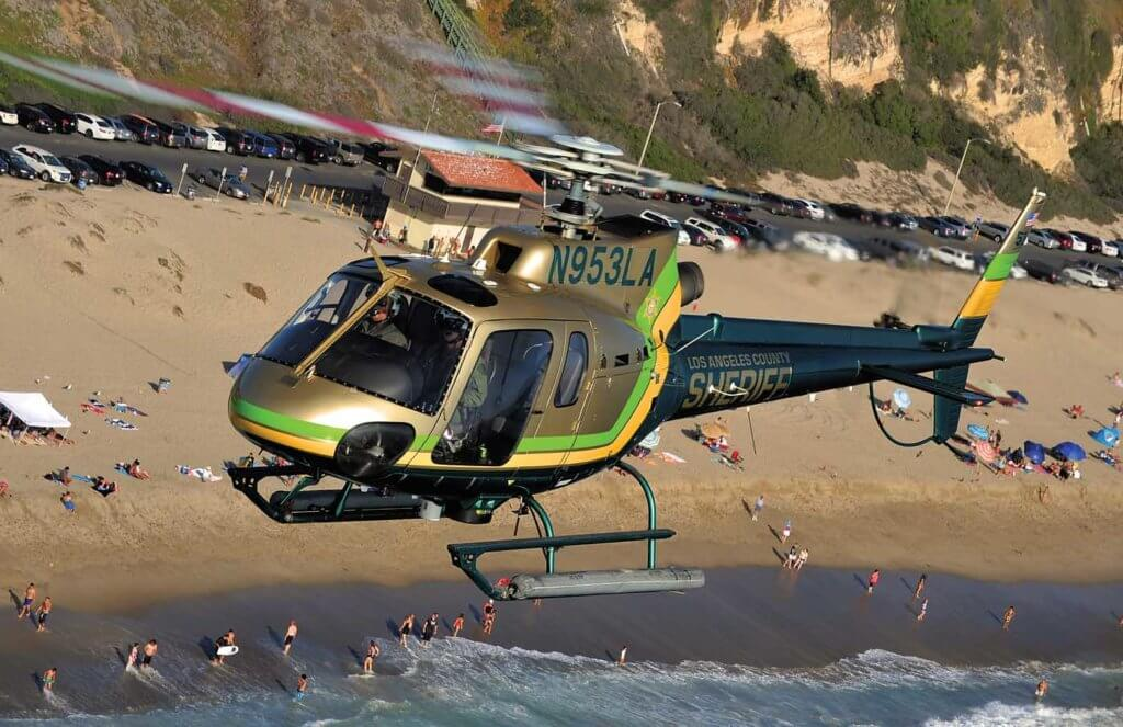 Helicopter in flight above beach.