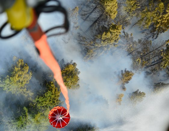 An Oregon Army National Guard CH-47 Chinook helicopter with 1st Battalion, 168th Aviation Regiment dups a 2,000 gallon capacity Bambi Bucket amid smoke over the Mt. Jefferson Wilderness Area in order to support firefighting efforts on the Whitewater Fire on August 5, 2017.