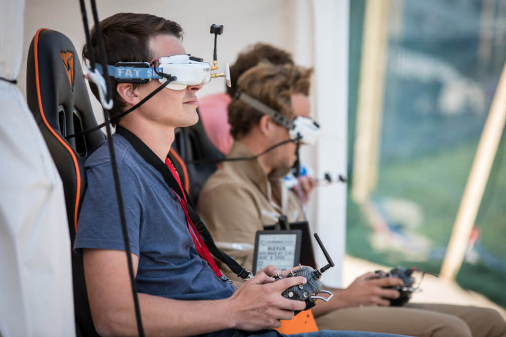 Droner racers wear immersive headsets that give the user a first-person view from the drone as fly around a course. FAI Photo