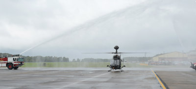 An OH-58D Kiowa Warrior passes through water from fire trucks after its final flight at Joint Base Langley-Eustis, Virginia. U.S. Air Force Staff Sgt. Teresa J. Cleveland Photo