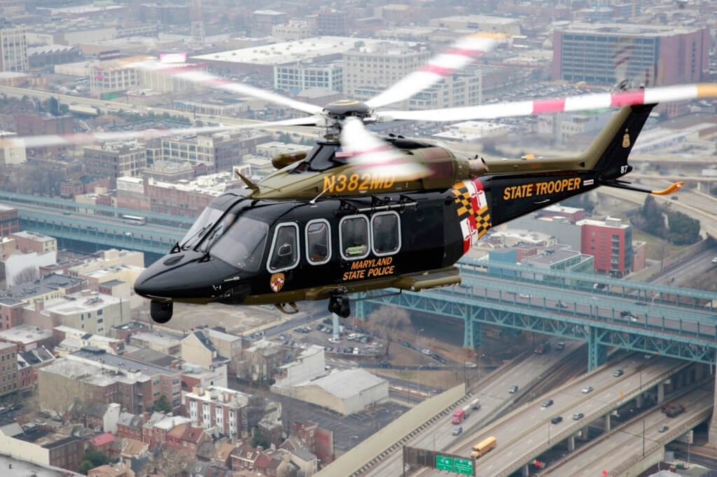 A Leonardo AW139 from the Maryland State Police flies over a cityscape.