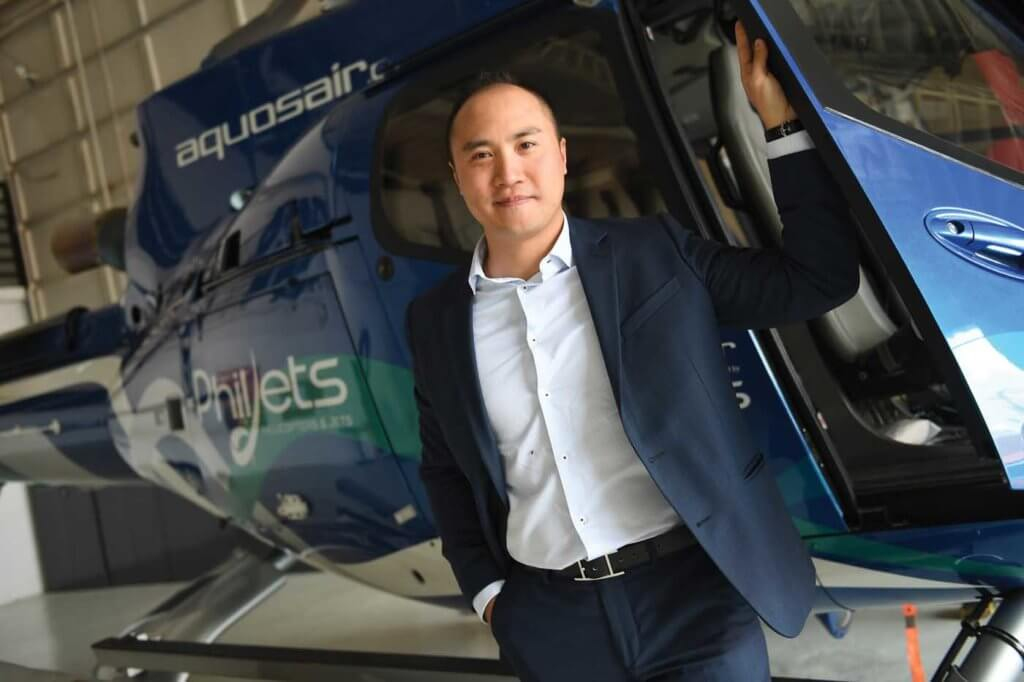Thierry Tea stands next to a PhilJets helicopter.