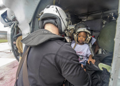 Naval Aircrewman (Helicopter) 2nd Class Logan Parkinson, assigned to Helicopter Sea Combat Squadron (HSC) 22, prepares a patient's family for evacuation during relief efforts in the wake of Hurricane Maria in St. Croix, U.S. Virgin Islands, Sept. 21. U.S. Navy MC3 Levingston Lewis Photo