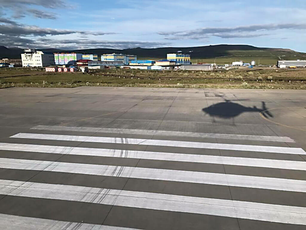 Helicopter casts a shadow on the tarmac.
