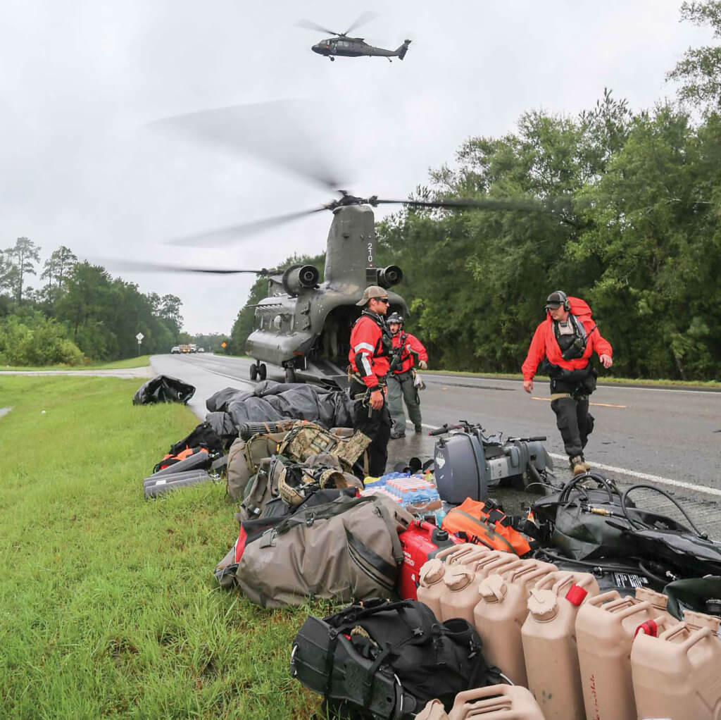 Alaska and California Air National Guardsmen unload search-and-rescue equipment from a Texas Army National Guard CH-47 Chinook helicopter from the 2-149th General Support Aviation Battalion.