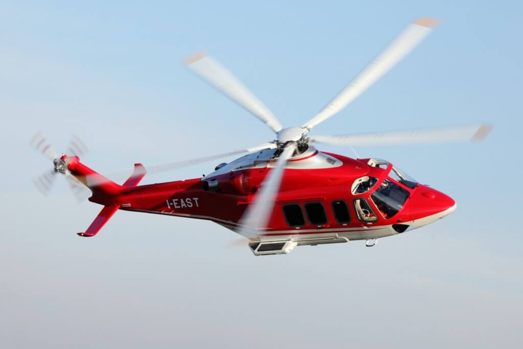Red AW139 helicopter in flight
